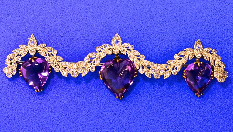 Antique heart shaped, buff-topped natural amethysts are suspended from a platinum and rose cut diamond garland.  The natural 3 amethysts are prong set in 18k yellow gold.  The platinum and diamond garland is well done exhibiting fine early 20th