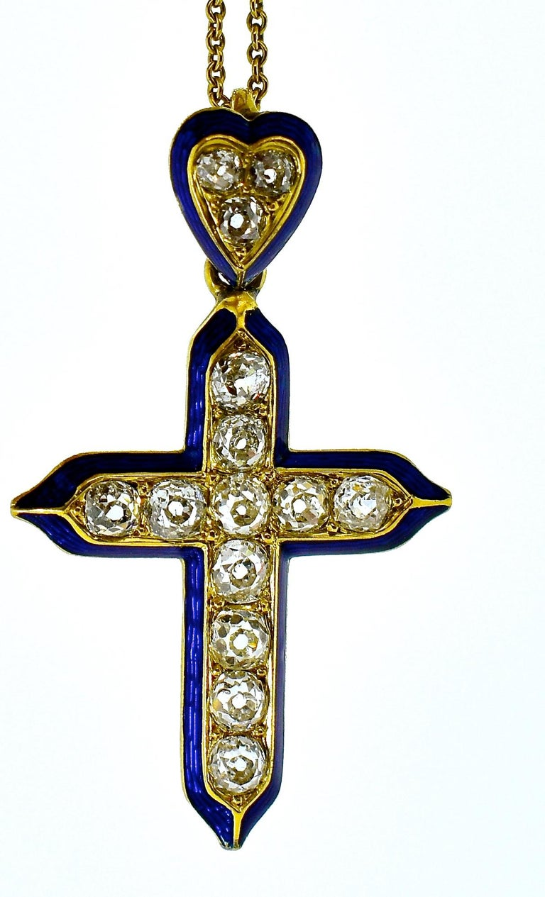Antique Cross composed of old cut diamonds, 14 in total, all near colorless and slightly included, total estimated weight of these stones is 2.20 cts.  There is cobalt blue enamel outlining the cross which is suspended from a heart shaped bale.  The