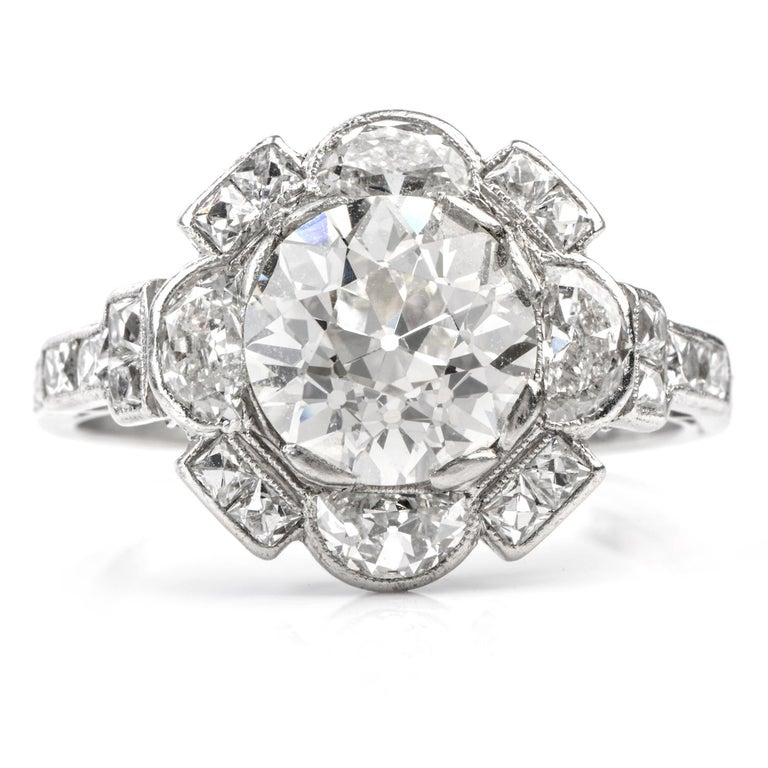 This Antique bright and vivid Diamond Engagement Cocktail Ring was inspired in a   floral motif and crafted in Luxurious Platinum.  Featuring a round Old European Cut Diamond in the center weighing appx. 2.26 carats,   this diamond is of I color and