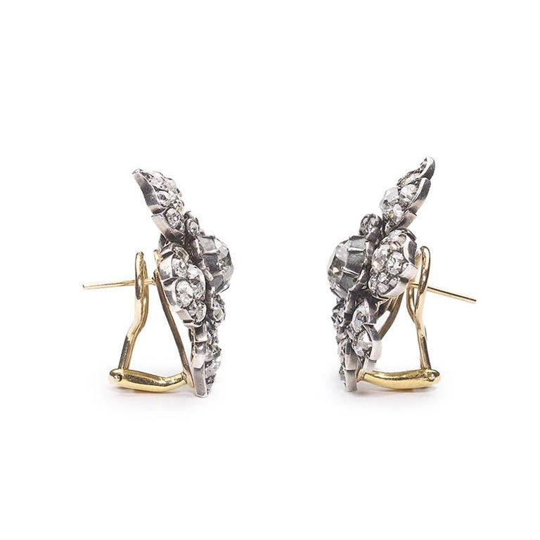 A pair of antique diamond flower earrings, set with approximately 9.00ct of old-cut diamonds, in total, with the principle cushion shaped diamond weighing approximately 1.50ct, in each, in cut down settings, with a surround of old-cut diamonds, in