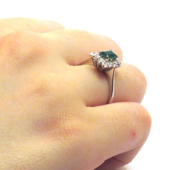 1960s white gold ring with natural emerald and 14 diamonds round cut. Emerald size: 6x4 millimeters / 0.236x0.157 inches, 0.40 ctw. Diamonds weight: approximately 0.45 ctw. Ready for delivery. It can be shipped with express delivery on