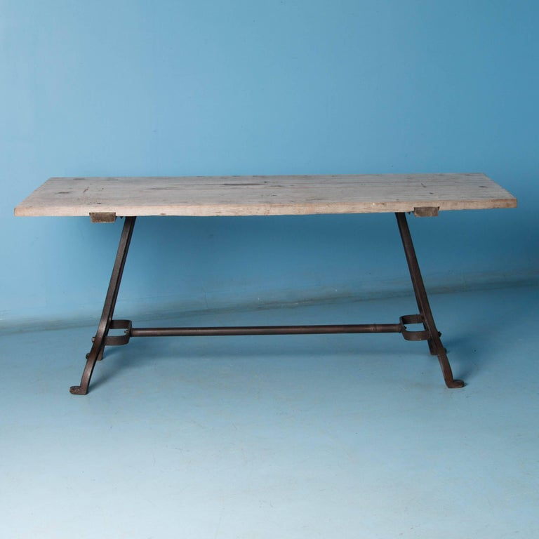This eastern European dining table with rustic industrial charm, features antique cast iron legs and a hardwood plank top. The distressed silver painted top has the patina of weathered gray wood while the base is a dark gray, almost black, waxed