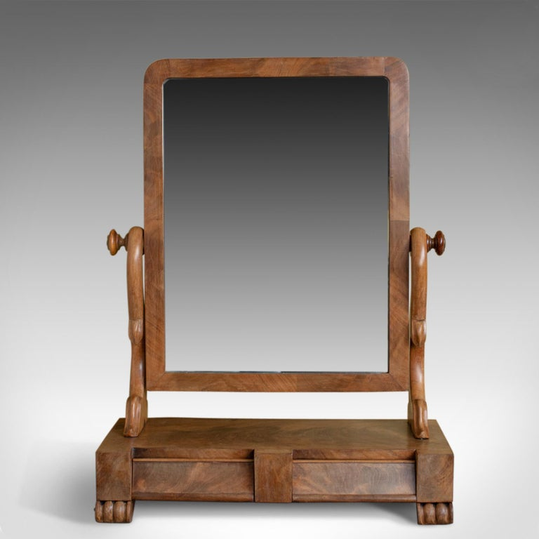 This is an antique dressing table mirror, an English, Victorian mahogany, adjustable swing mirror dating to circa 1870.