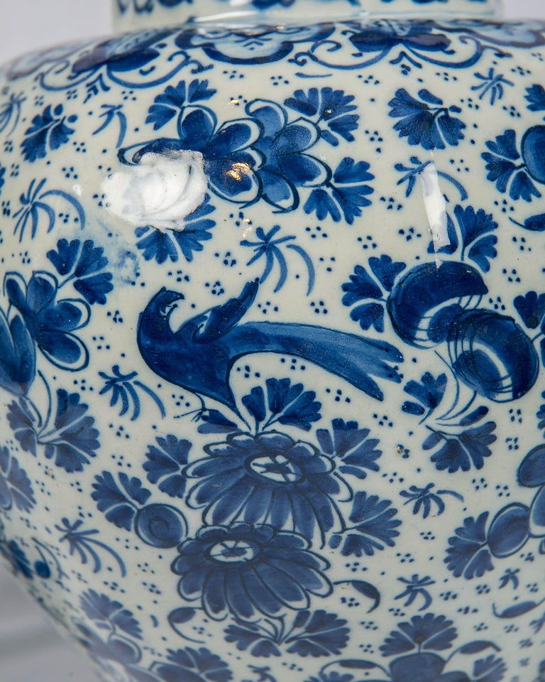 An antique Dutch delft blue and white three-piece garniture consisting of a pair of gourd shaped vases and a single covered vase made circa 1700-1716. This grouping is truly beautiful. All three vases have the mark of Peter Gerritsz. Kam of De Drie