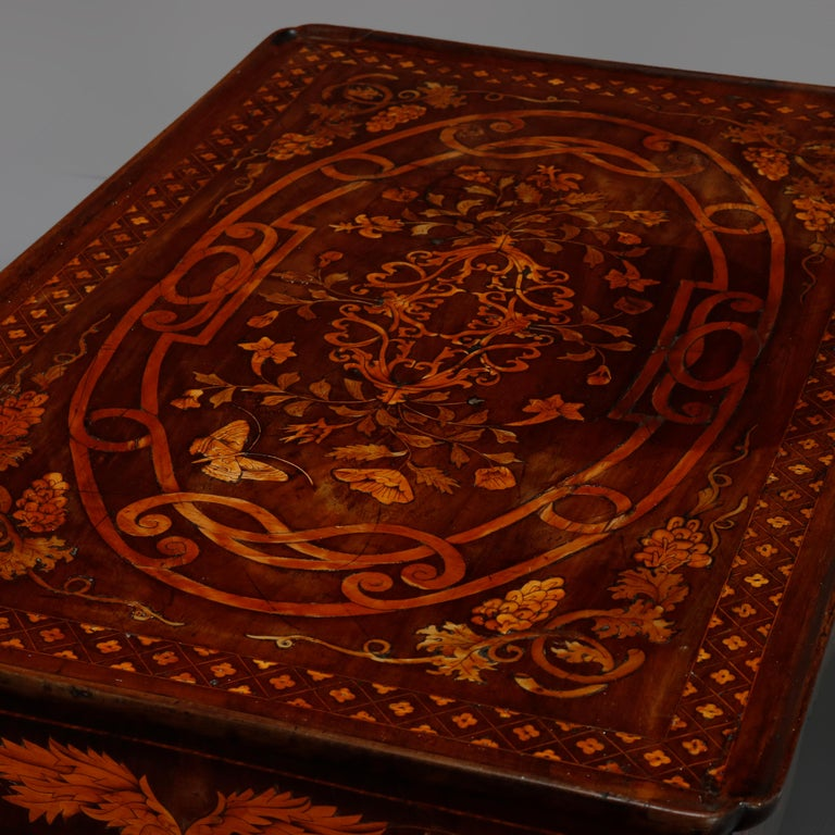 An antique Dutch marquetry table offers walnut construction with marquetry top having satinwood grape and leaf inlaid design and shaped skirt having central shield and flanking foliate and floral decoration, banding throughout, raised on foliate