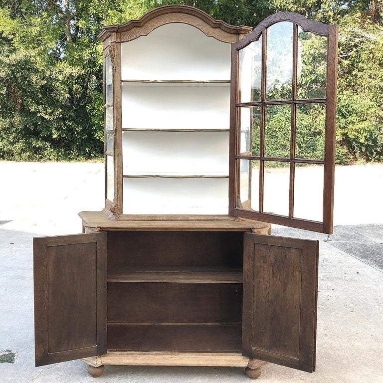 Antique Dutch Stripped Oak Bookcase is the perfect choice for displaying your book collection, or any collection for that matter! Arched crown and fine molded detail abound from the top to the bottom, with a spacious cabinet featuring serpentine