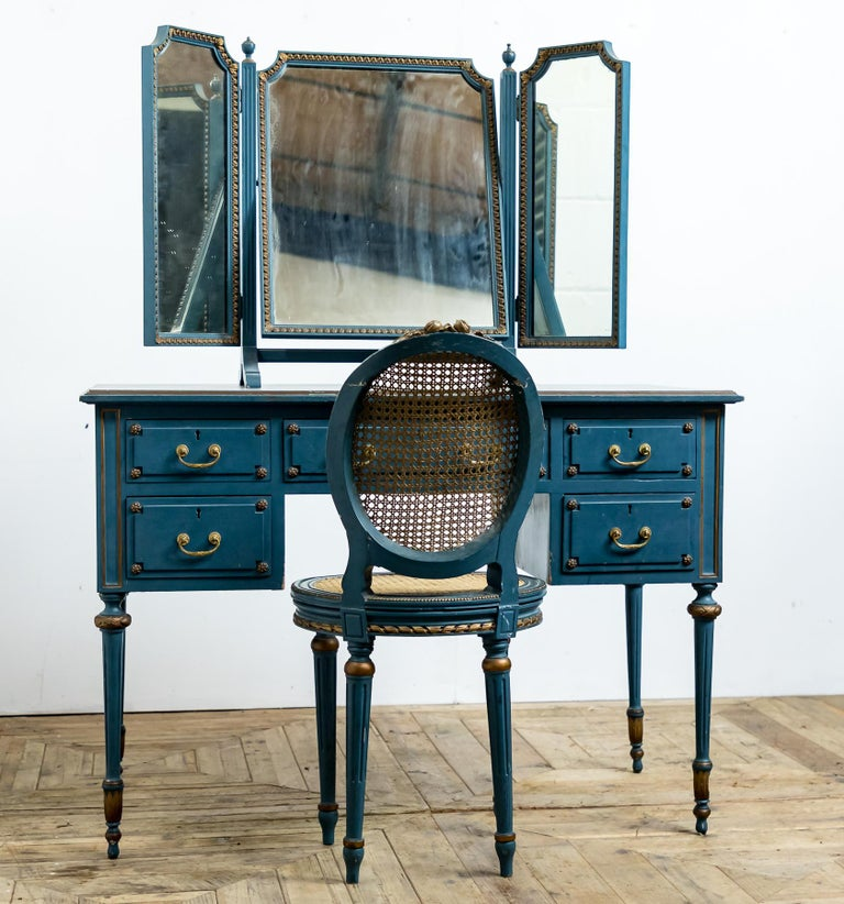 A lovely blue painted dressing table with triptych mirror and bergere chair. In the original paint with gold highlights and gilt brass fittings.  Date: Early to mid-20th century circa 1930-1950.  Approx. Dimensions: Dressing table - 109cm