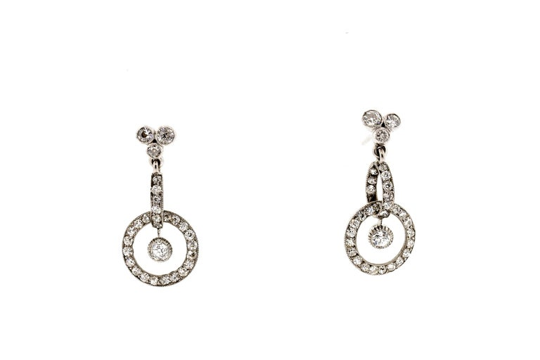 Early 20th Century platinum diamond earrings, circa 1910. These earrings are a pretty design, with a trefoil on top and two connecting dimensional loops on the bottom. They are set with 64 old European and single cut diamonds weighing approximately