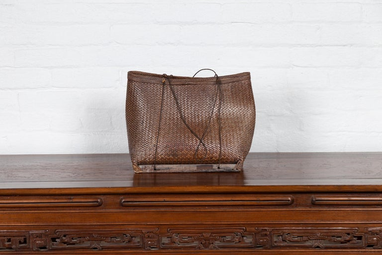 An antique early 20th century small woven grain basket from the Philippines with wooden base. Charming our eyes with its humble appearance, this woven basket reminds us of the history and use that gives it its charming character. Raised on a small