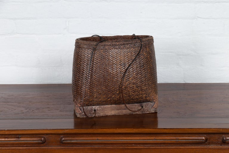 An antique early 20th century small woven carrying grain basket from the Philippines with wooden base. Charming our eyes with its nicely rustic appearance, this woven basket reminds us of the history and use that gives it its charming character.