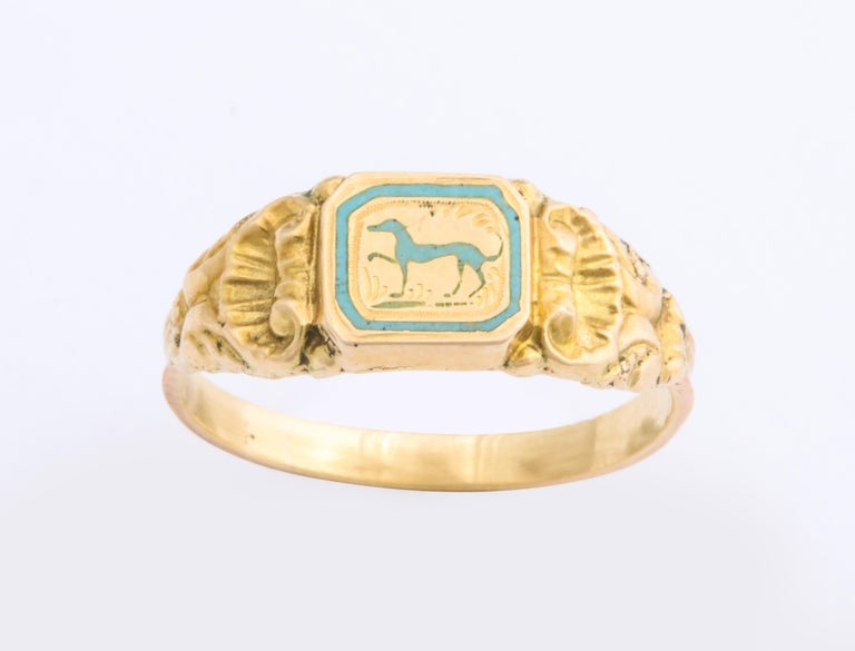 A French 18 Kt gold ring c. 1840, likely the only one ever made, depicts a greyhound or whippet in pale aqua with one leg gracefully raised in a prance. and head erect. The dog is bordered by an aqua frame that strengthens the design. Engraved marks