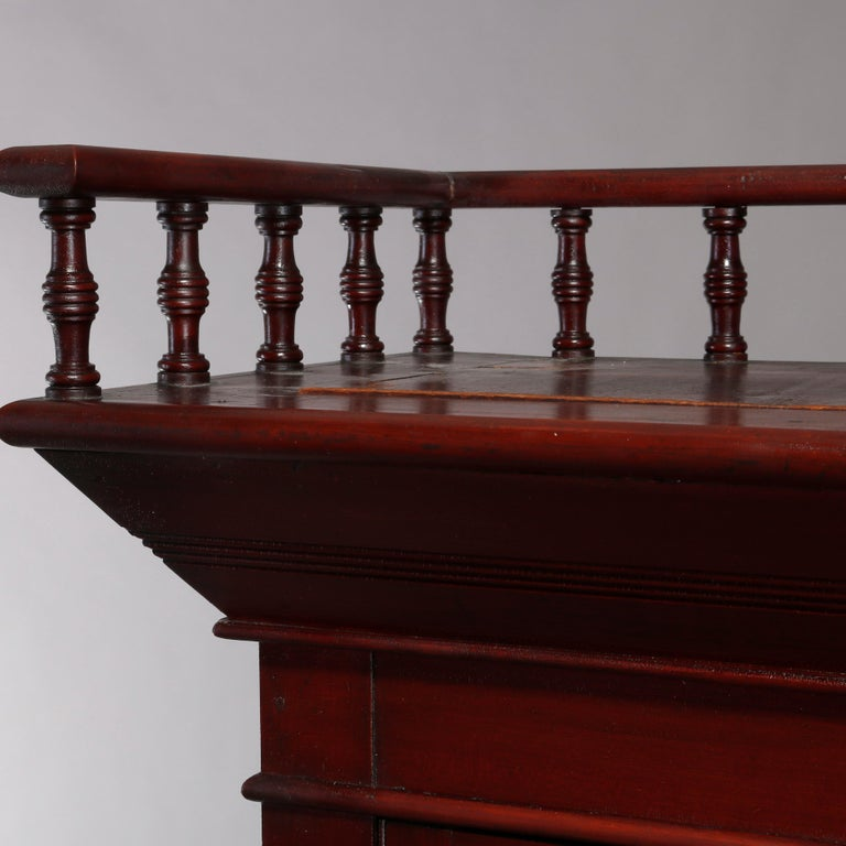 An antique Eastlake bookcase offers mahogany construction with upper gallery having spindled rail surmounting case with double glass doors opening to shelved interior and over double lower drawers, circa 1900