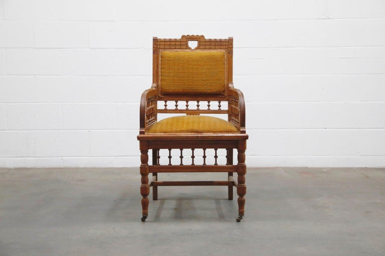 Antique Eastlake oak armchair with fabric seat and seat-back on top of front caster legs. Interesting carved detailing and turned wood posts. Would make a great hall-chair or study room armchair.  This beautiful 19th century chair would work great
