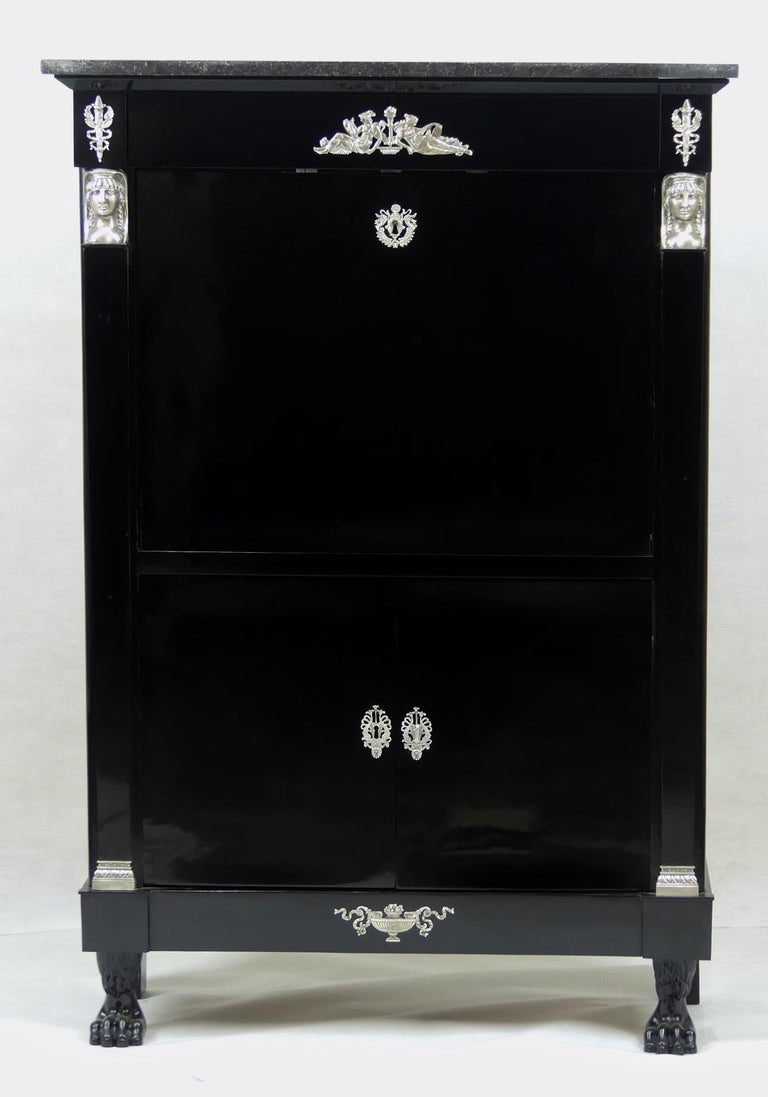 An original antique Empire secretary from the early 19th century from France. The secretary is ebonized and has wonderful silver plated fittings.  The secretary has two main compartments and an original marble top. The first compartment covers the