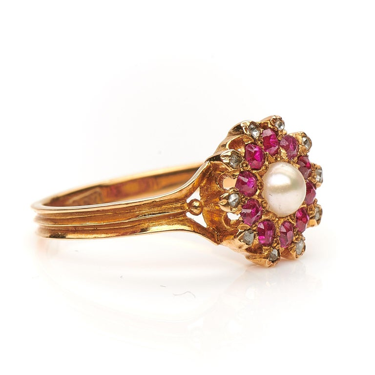 Edwardian, ruby, diamond and pearl dress ring, circa 1910. Set to centre a natural spilt pearl framed by rubies with an outer boarder of rose-cut diamonds. The wonderful colour combination is what makes this ring unique, the cluster is a burst of