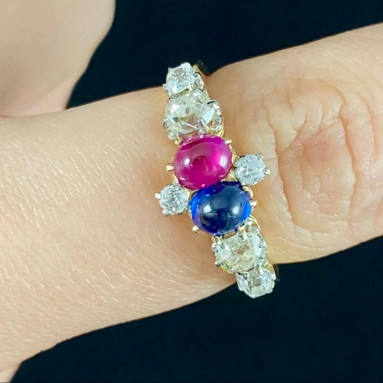 Antique Edwardian Sapphire, Ruby and Old Cut Diamond Ring in Gold, c. 1915. This jewel consists of a central cruciform motif composed by two Old European brilliant-cut diamonds and two cabochon gemstones of probably Burmese origin - a royal blue