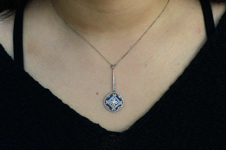 A stunning antique, this lavalier style necklace is eminently wearable. With a velvety blue enamel serving as the canvas for the 40 rose cut diamonds set in an interesting lattice pattern. The drop style filigree pendant dangles from a single,