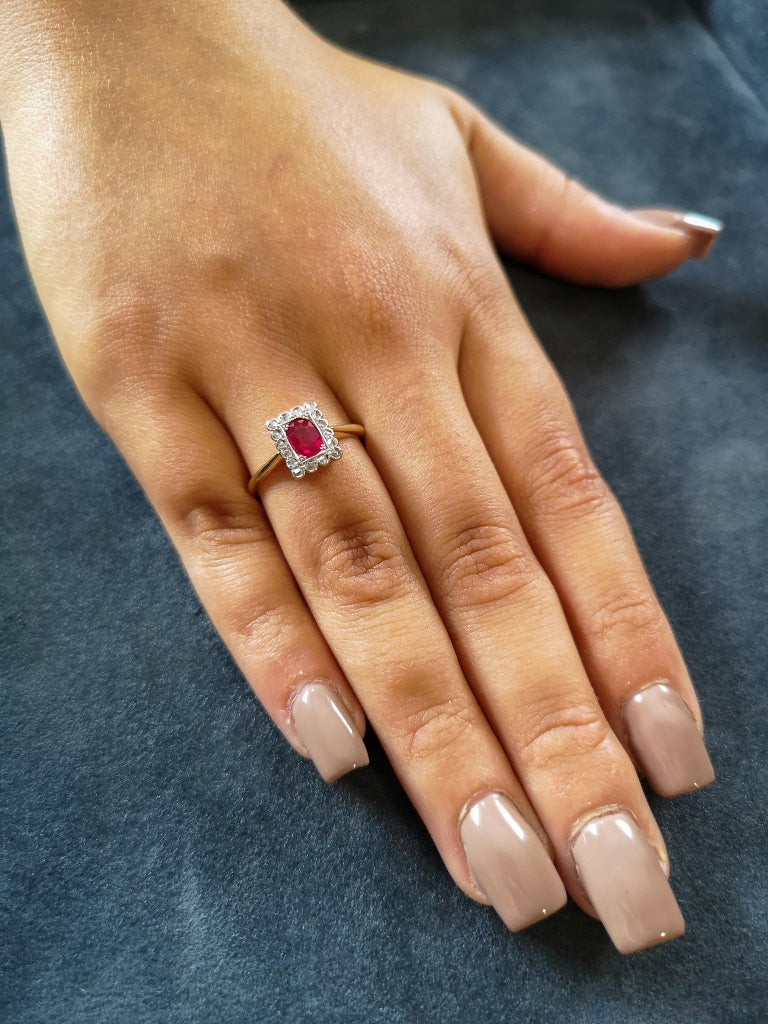 An exquisitely beautiful & timeless Edwardian cluster engagement ring comprising a blood-red oval-cut ruby, mounted with a halo of rose-cut diamonds in platinum. Setting: 18-carat yellow gold shank with knife-edge shoulders - Stamped 18ct Plat