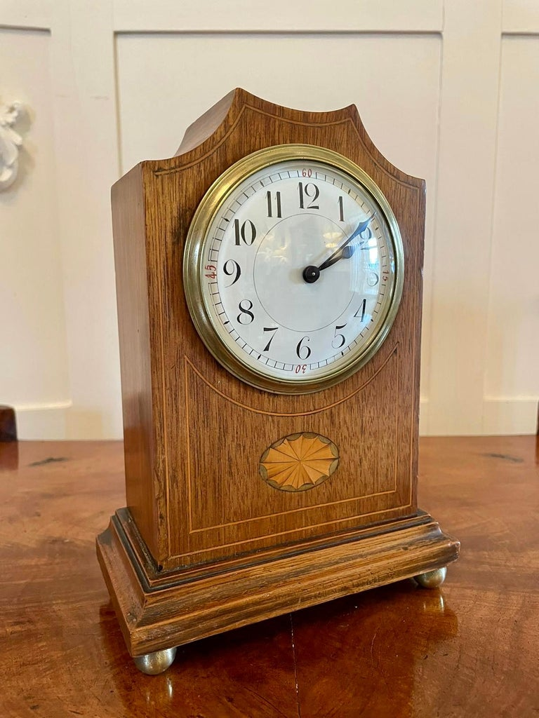 Antique Edwardian inlaid mahogany eight day mantel clock having a pretty shaped top mahogany case inlaid with boxwood stringing and an oval satinwood shell, enamel dial with original hands, brass beze. It stands on a shaped plinth with original