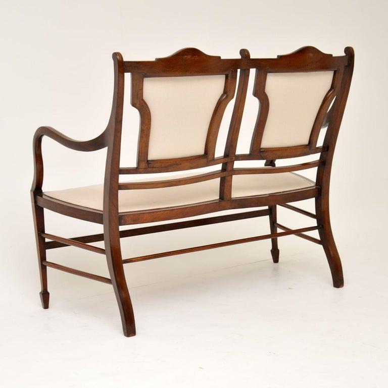 Very elegant antique Sheraton style mahogany settee dating from the 1890-1900 period and in good original condition. There are a few age related markings on the frame, but they have been polished out and everything is in character, plus it's