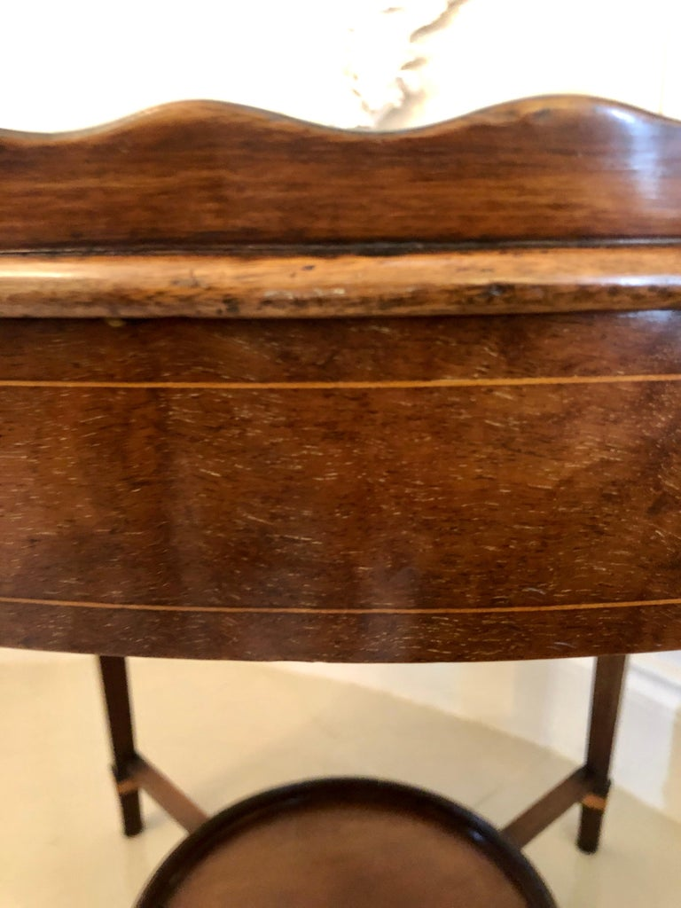 Antique Edwardian inlaid mahogany oval tray table having an oval inlaid mahogany tray top with inlay to the centre, two brass carrying handles and a pie crust edge and oval mahogany frieze. It stands on elegant square tapering legs with pretty oval