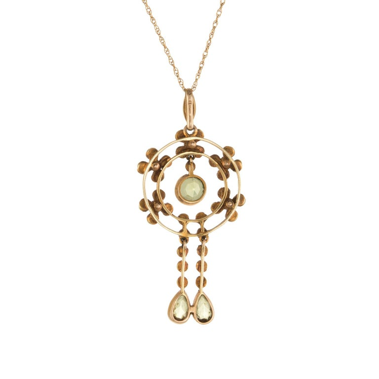 Finely detailed Edwardian era necklace (circa 1910s), crafted in 15 karat yellow gold with a 14 kart yellow gold chain.  Faceted round cut peridot (upper) is estimated at 0.60 carats, with two faceted pear cut peridot estimated at 0.50 carats each.