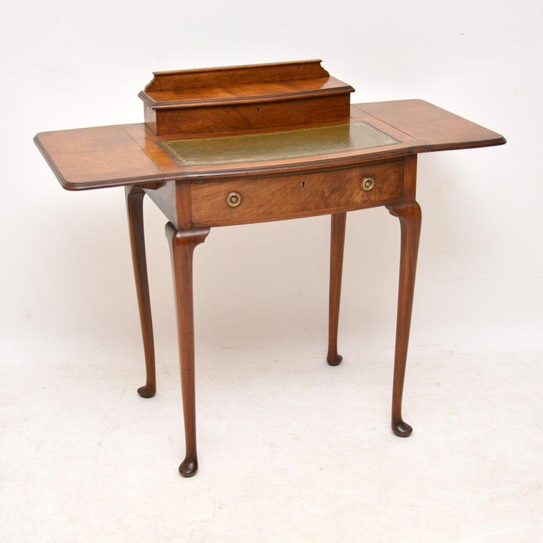 Small antique Edwardian walnut writing table with some very useful features. It's in excellent original condition and dates from circa 1910 period. This desk has a tooled leather writing surface and useful drop flaps which can extend the top surface