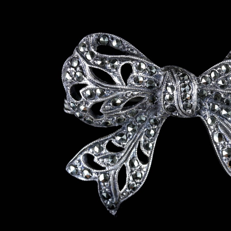 This beautiful Silver Edwardian bow brooch is adorned in Marcasites, Circa 1910.  During the Edwardian period jewellery became strikingly feminine with a lacy and delicate appearance. Bows very quickly became modern motifs.  The bow brooch shows