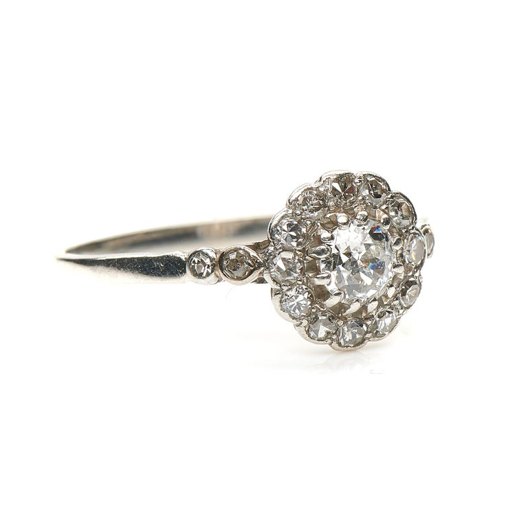 Antique, diamond engagement ring, circa 1910. Set to centre a round old cut diamond in a open-backed claw setting framed by a boarder of delicate smaller diamonds all rubover set in platinum. Further diamonds descend the shoulders to enhance the