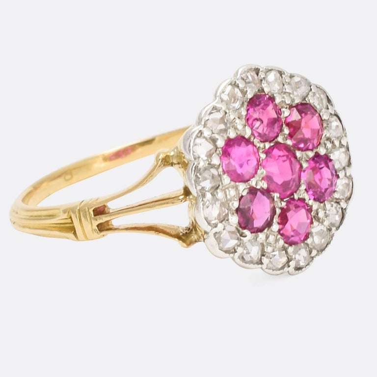 A sublime antique pavé cluster ring, the platinum head modelled as a stylised flower. It's set with seven bright rubies, within a cluster of 18 rose cut diamonds. With pretty trifurcated split shoulders and a grooved band, it's a very beautiful