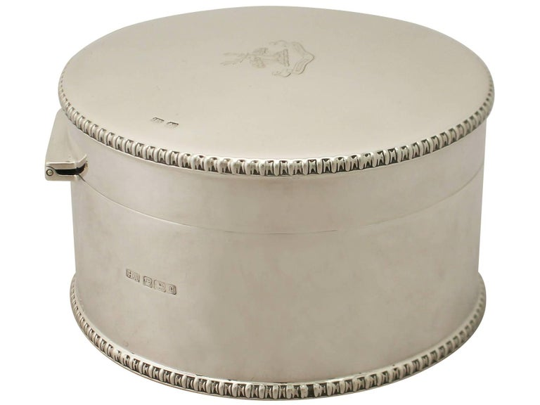 An exceptional, fine and impressive antique Edwardian English sterling silver biscuit box; an addition to our silver teaware collection.  This exceptional antique Edwardian sterling silver biscuit box has a plain circular form.  The surface of
