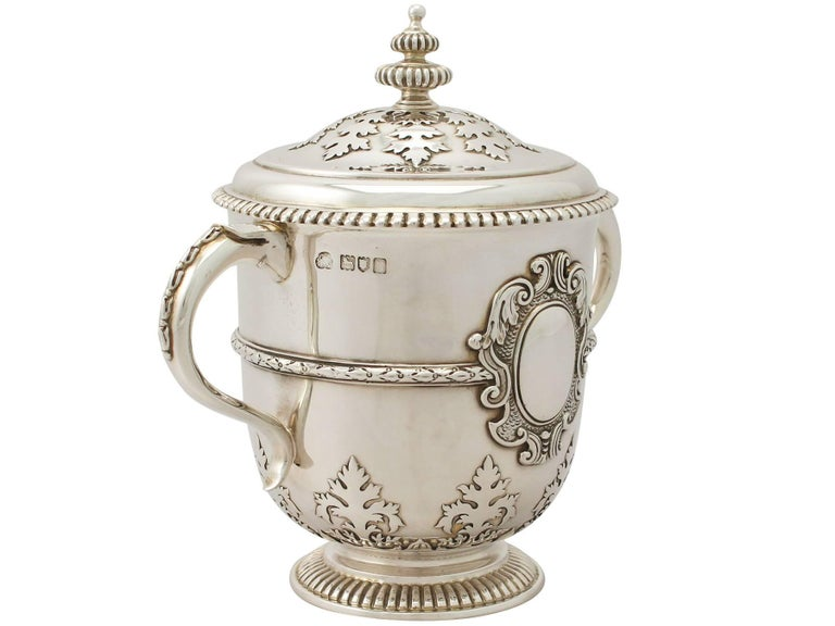 An exceptional, fine and impressive antique Edwardian English sterling silver cup and cover; an addition to our silver presentation collection.  This exceptional antique Edwardian sterling silver cup and cover has a circular bell shaped form onto