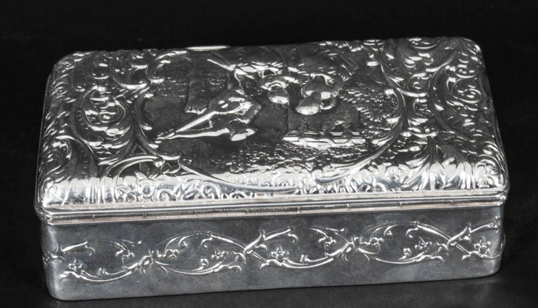 This is a lovely antique Edwardian sterling silver jewellery casket bearing the makers mark of H.Matthews, and hallmarks for Birmingham, 1901.  The rectangular hinged box cover is chased with figures in 18th century dress within a cartouche