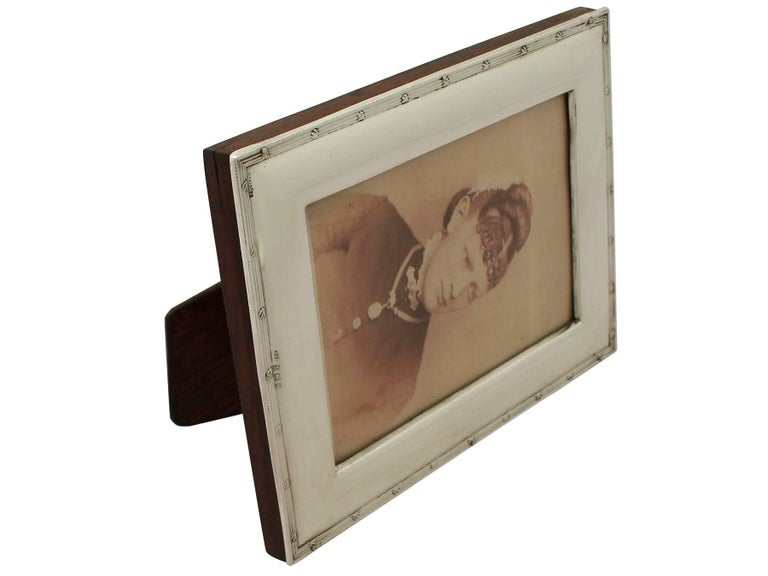 A fine and impressive antique Edwardian English sterling silver photograph frame, an addition to our ornamental silverware collection.  This fine antique Edwardian sterling silver photograph frame has a plain rectangular form.  The surface of this