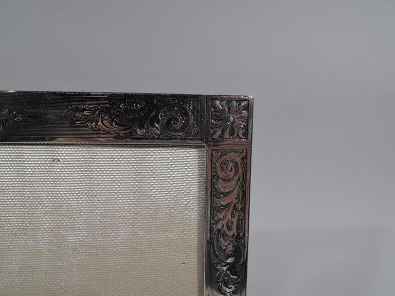 Edwardian sterling silver picture frame. Made by Birks in Canada, circa 1910. Rectangular window and flat surround with wraparound engine-turned lines and chased leafy scrolls and corner paterae. At top shaped rectilinear cartouche (vacant). With