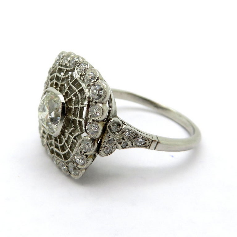 Antique Edwardian style platinum spider web motif diamond engagement ring. Centering one Old Mine cut milgrain bezel set diamond weighing approximately 0.95 carats, having J color grade and VS1 clarity grade. Accented with 30 Old European cut