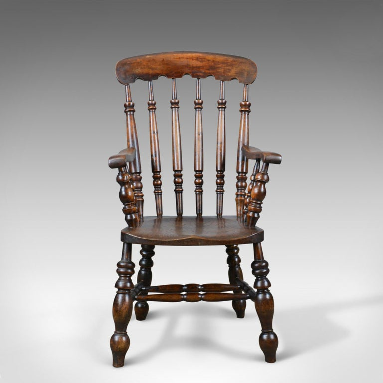 This is an antique elbow chair, an English, Victorian stick-back Windsor chair in elm dating to the late 19th century, circa 1880.  Appealing color and a desirable aged patina Grain interest to the thick elm, saddle seat slab Attractive, notched