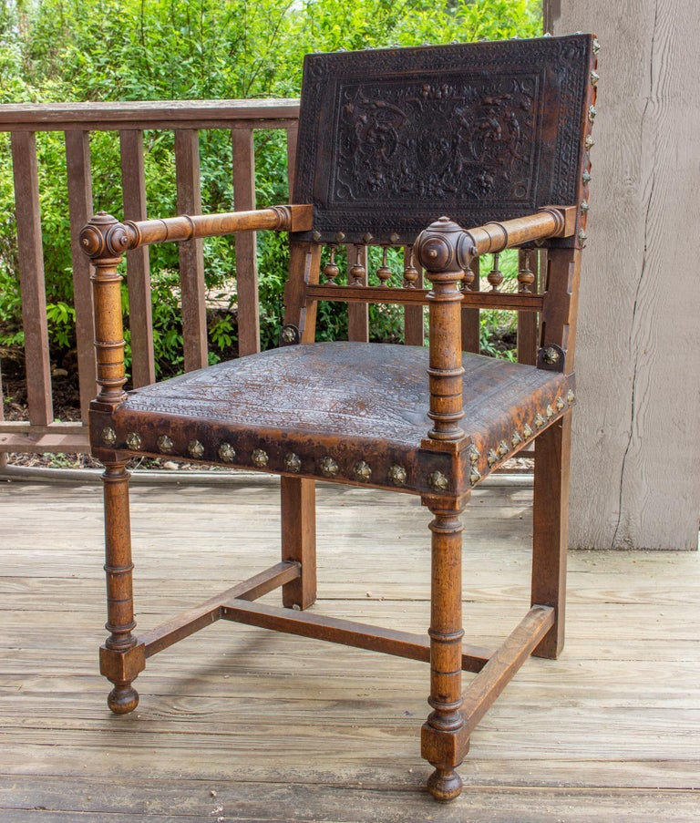 This beautifully worn antique armchair is crafted with a solid wood frame and rich, deep brown embossed leather. The designs are primarily depictions of animals, trees and leaves surrounded by decorative borders on both the seat and the chair back.
