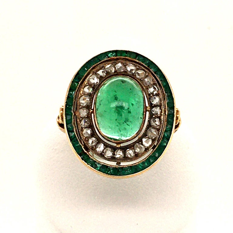 Antique filigree ring with lots of charme. The Emerald Cabochon weighs approx. 2.40 ct, has a lively green and good transparancy.  To ensure that he is staged correctly, 24 sparkling diamond roses set in silver and another row of emeralds surround