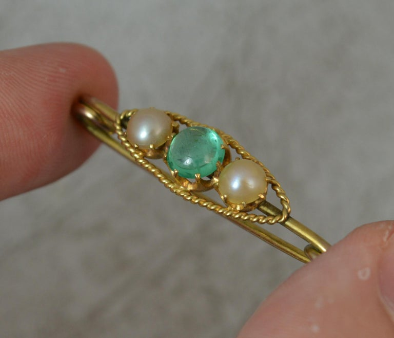 A very well made true Victorian period pin brooch. Solid 15 carat yellow gold example. Designed with a single round emerald cabochon to the centre with a pearl to each side. 6.1mm diameter emerald.  Condition ; Very good. Crisp pattern. Issue free.
