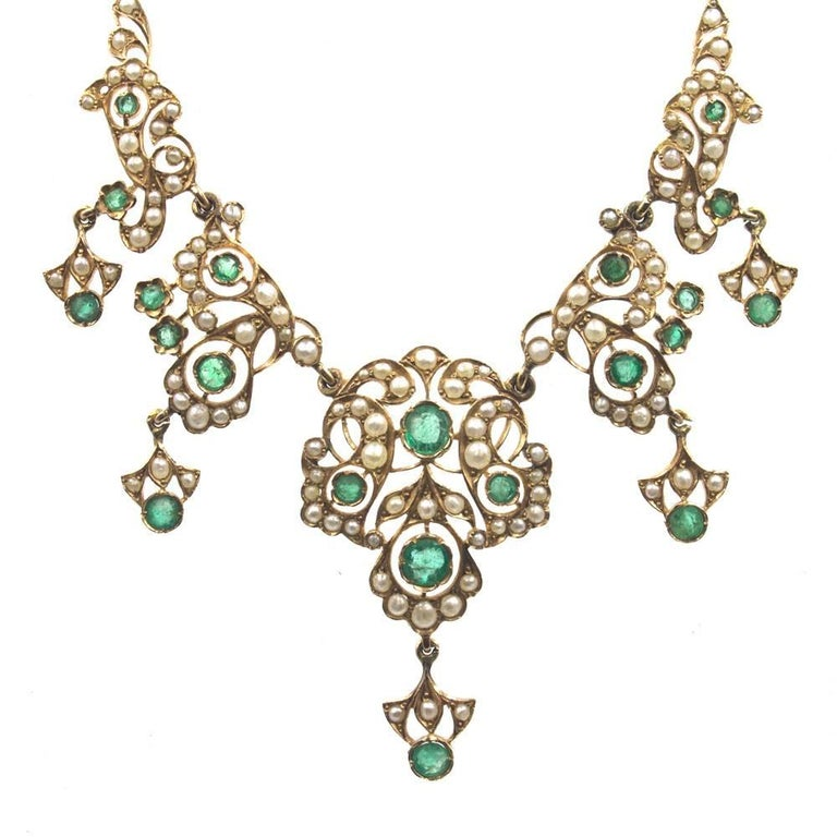 This beautifully crafted antique necklace features emerald and seed pearls set in 14 karat yellow gold. The necklace, circa late 19th Century, has a delicate open feel to it. The necklace measures 15.25 inches in length, and the emerald pearl drops