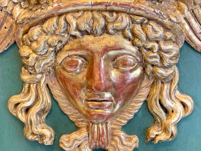This beautiful head of Hermes wearing his winged helmet is carved out of boxwood and has preserved the original gilding. The head is mounted on a blackened oak board retaining it's original seagrass green paint. This unusual relief was made in