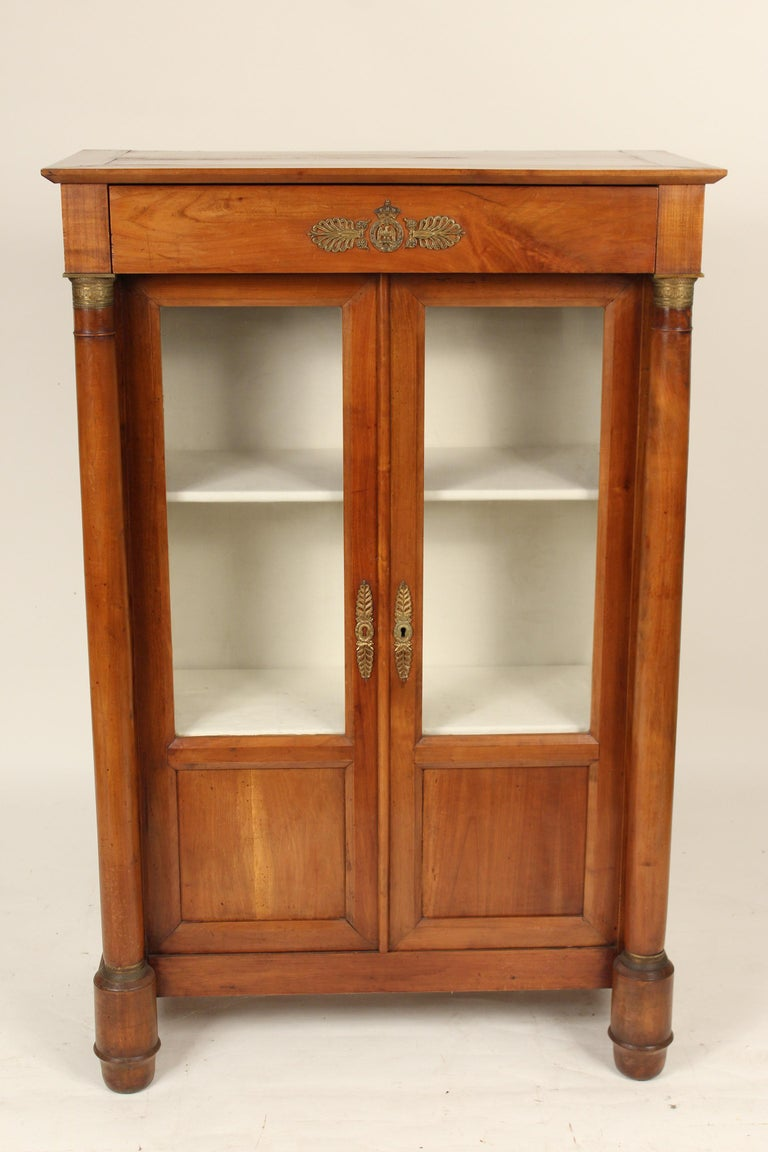 Antique Empire style beech wood and mahogany bookcase / display cabinet with brass hardware, late 19th century.