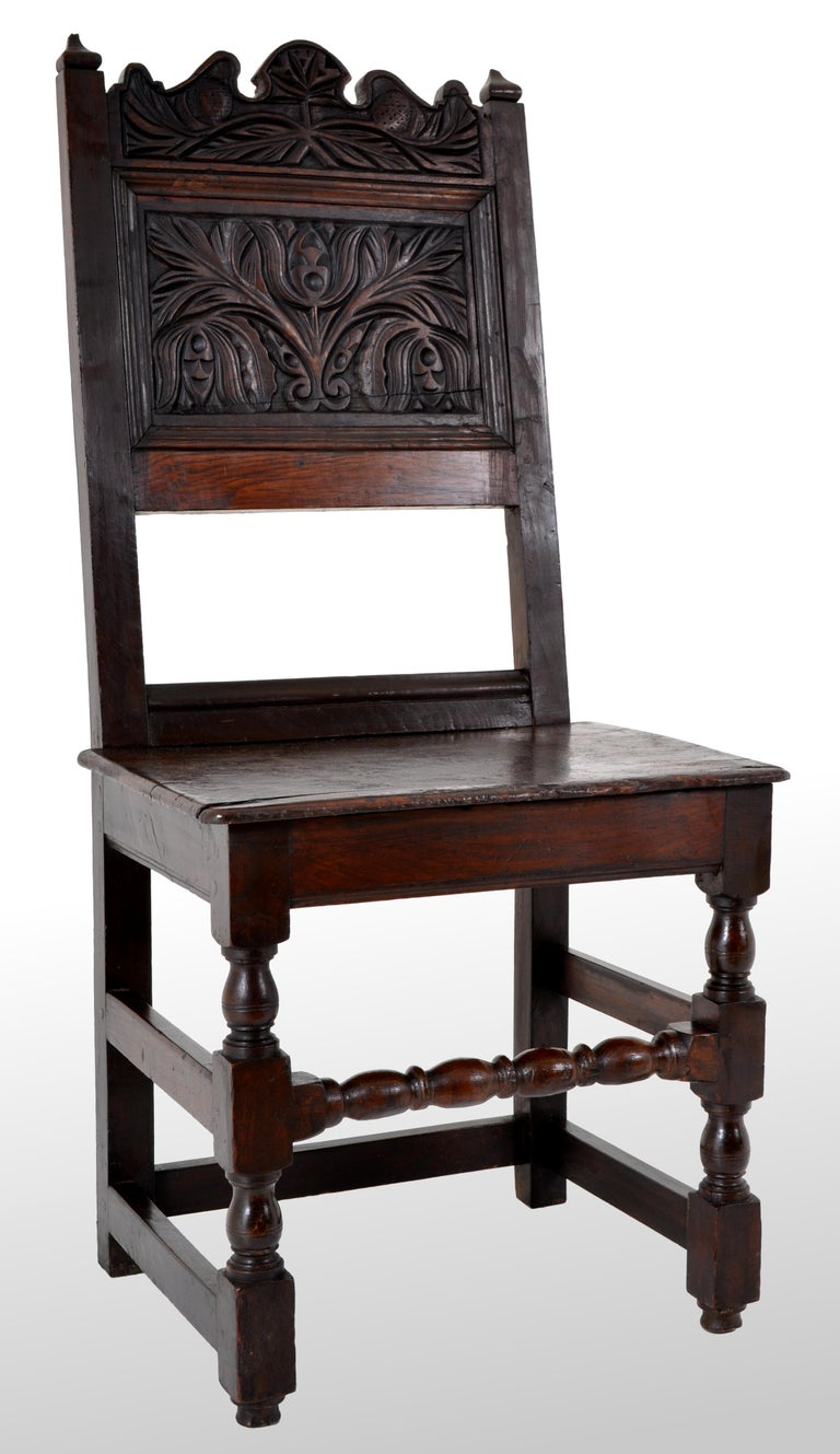 A Jacobean period carved oak chair, circa 1640. The chair having twin finials with a carved panel below with a stylized floral design. The chair having turned legs and a 'bobbin' turned stretcher, the chair of joined and pegged construction.