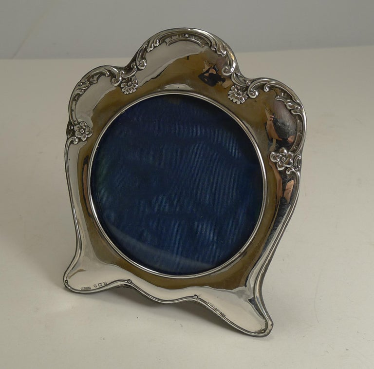 A very stylish Art Nouveau photograph frame made from English sterling silver with a full hallmark for Birmingham 1906, Edwardian in era. The makers initials are also present for the silversmith, Munsey and Co. Ltd. This frame is lucky enough to
