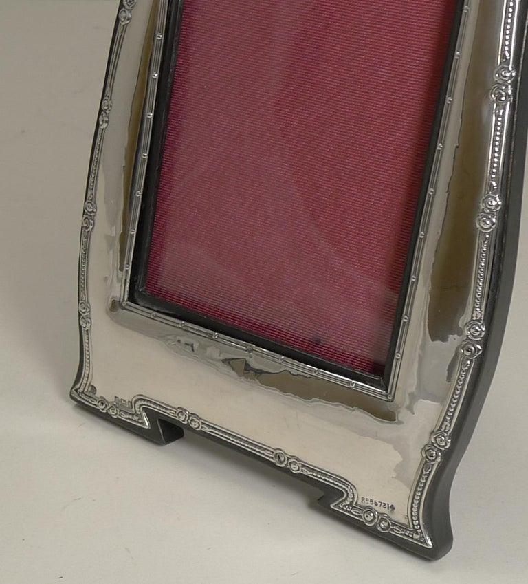 A very elegant photograph frame with an organic Art Nouveau shape outlined by a raised border.  The silver hallmark can be found on the left hand integral