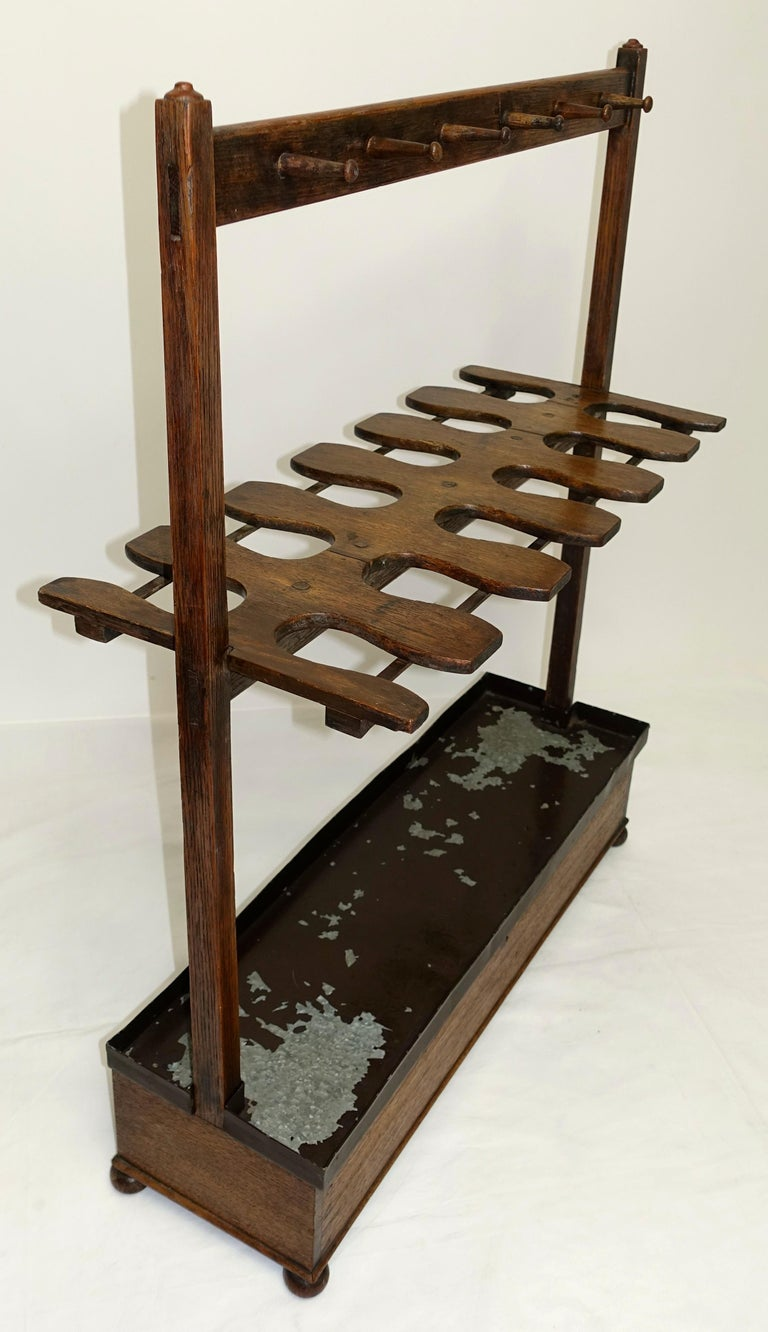 Late Georgian six pair boot rack made of English oak wood. Functional form with through mortise and tenon construction, and upright standards topped with small turned buttons. 12 pegs hold crops, whips and leather laces. The dovetailed top hinged