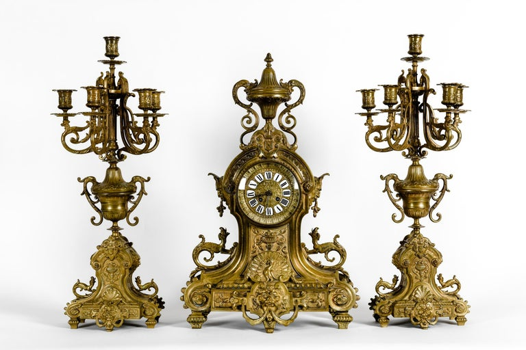 Antique English bronze renaissance revival three-piece clock garniture. The set composed of a center clock and two flanking six arms candelabra. Each piece is lavishly decorated with lion heads, winged caryatid, and serpents. Accented overall with
