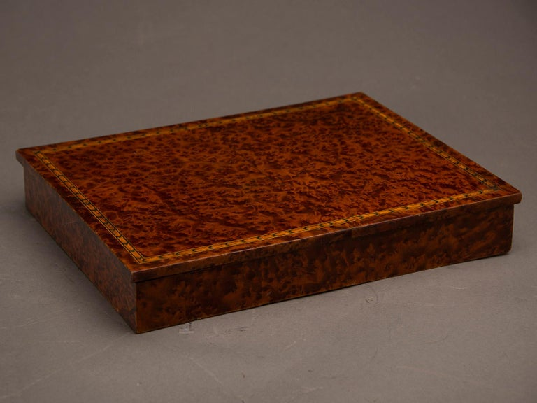 An unusual antique English burl walnut rectangular box from England, circa 1890. Please notice that the broad expanse of the top has an inlaid border close to the perimeter in a multicolored arrow pattern with three different colors of wood. This