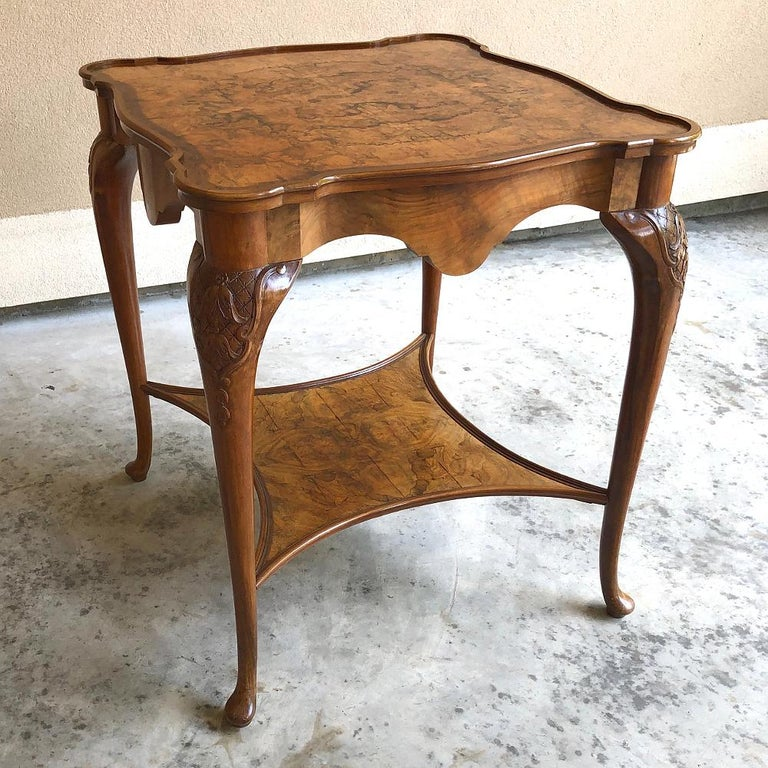 Antique English Chippendale tea table with tray was fashioned from imported walnut, and features the traditional cabriole legs with broad shoulders, a webbed shelf below, and a glass tray top that adds a level of sophistication and